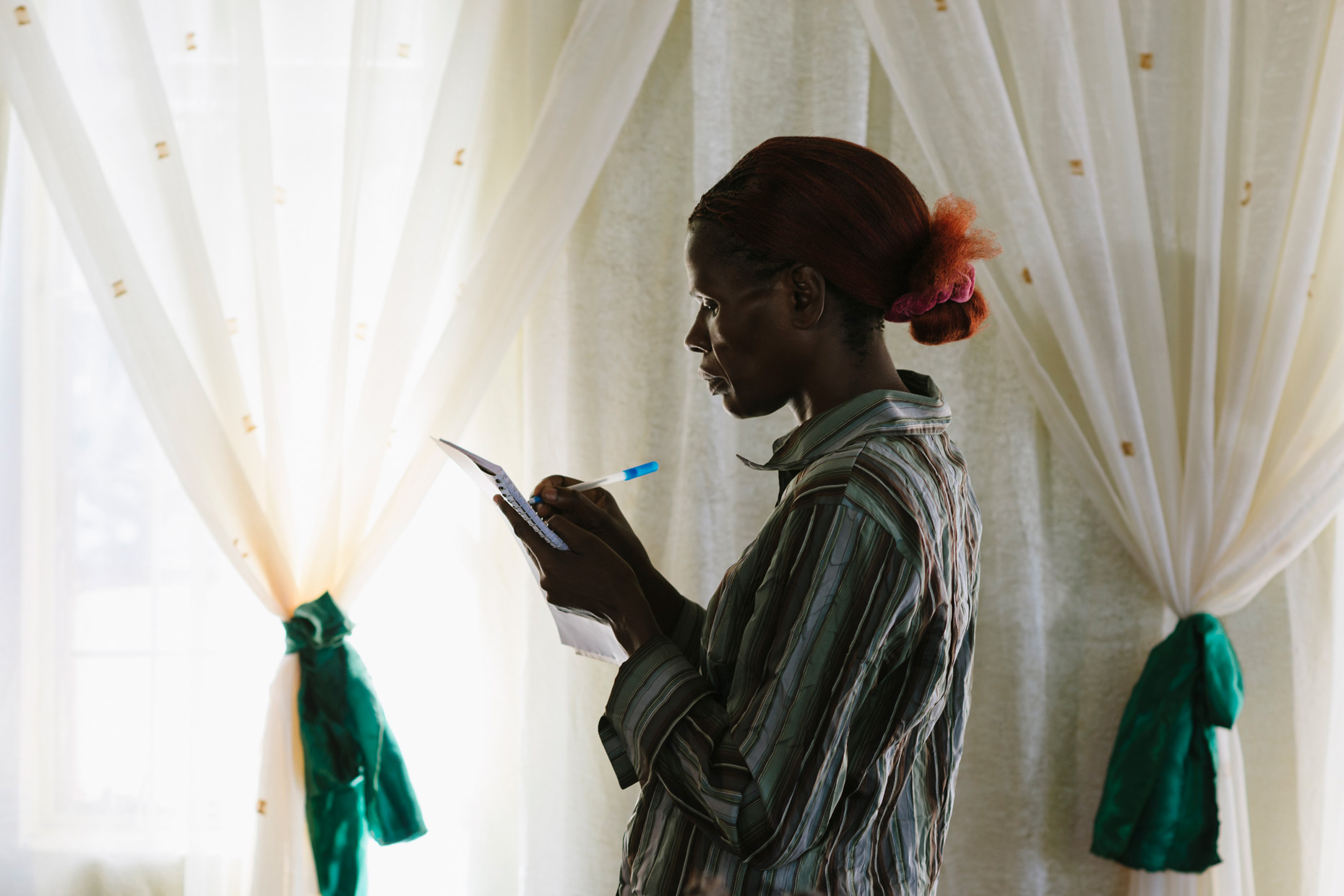 African-woman-writing-on-notepad-by-curtains-with-bows-YES