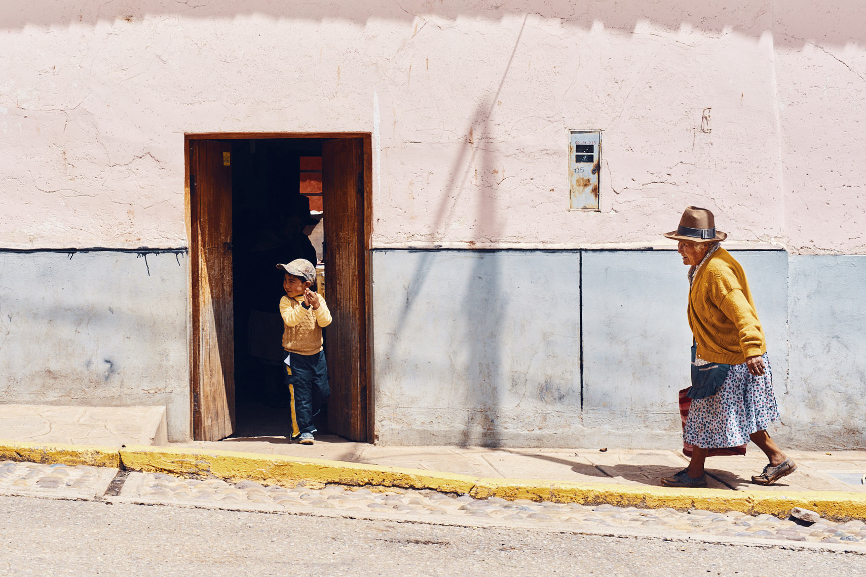 Elderly-Peruvian-woman-in-tall-hat-walking-on-sidewalk-with-young-boy-in-doorway