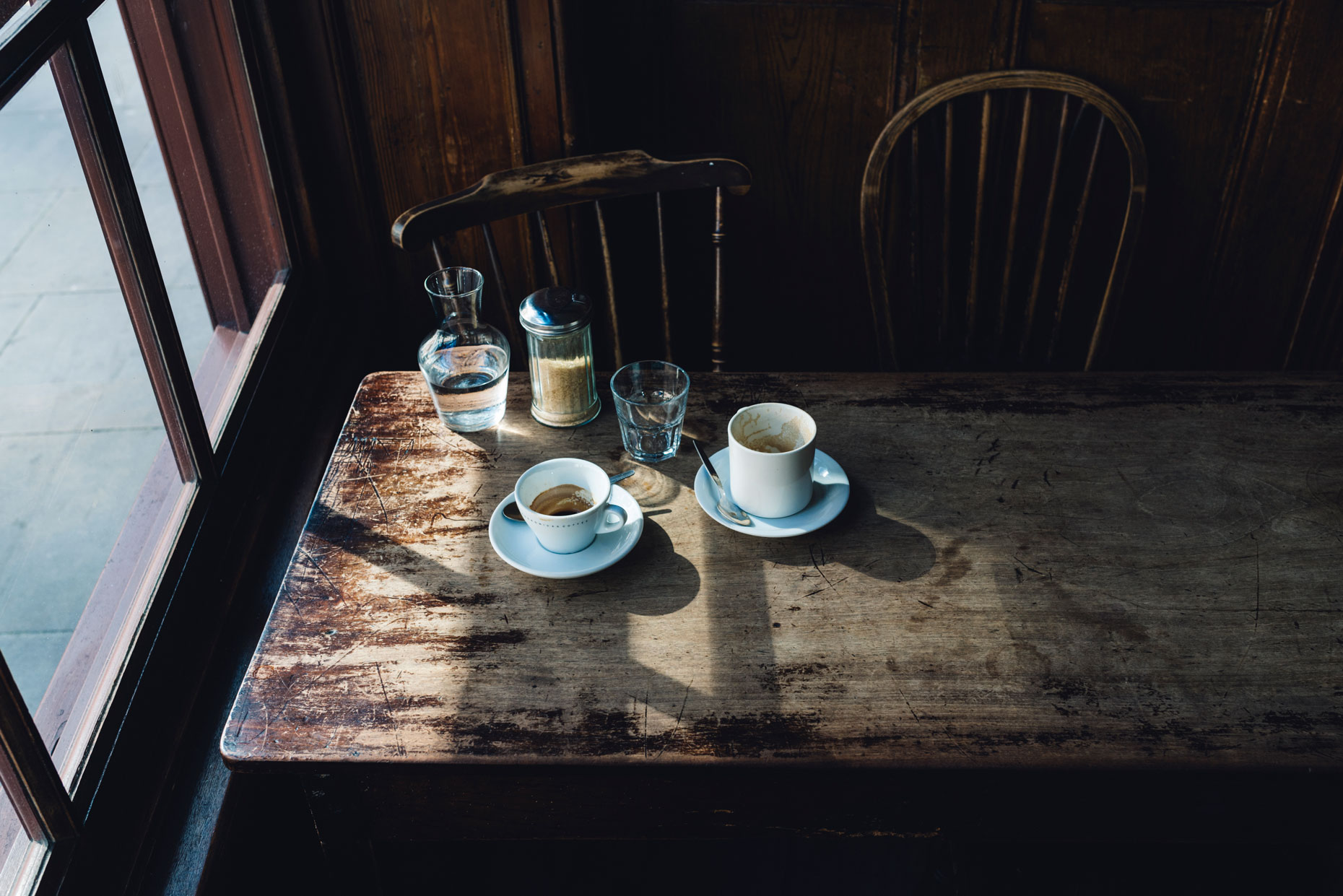 Empty-coffee-cups-on-shabby-wooden-table-in-cafe