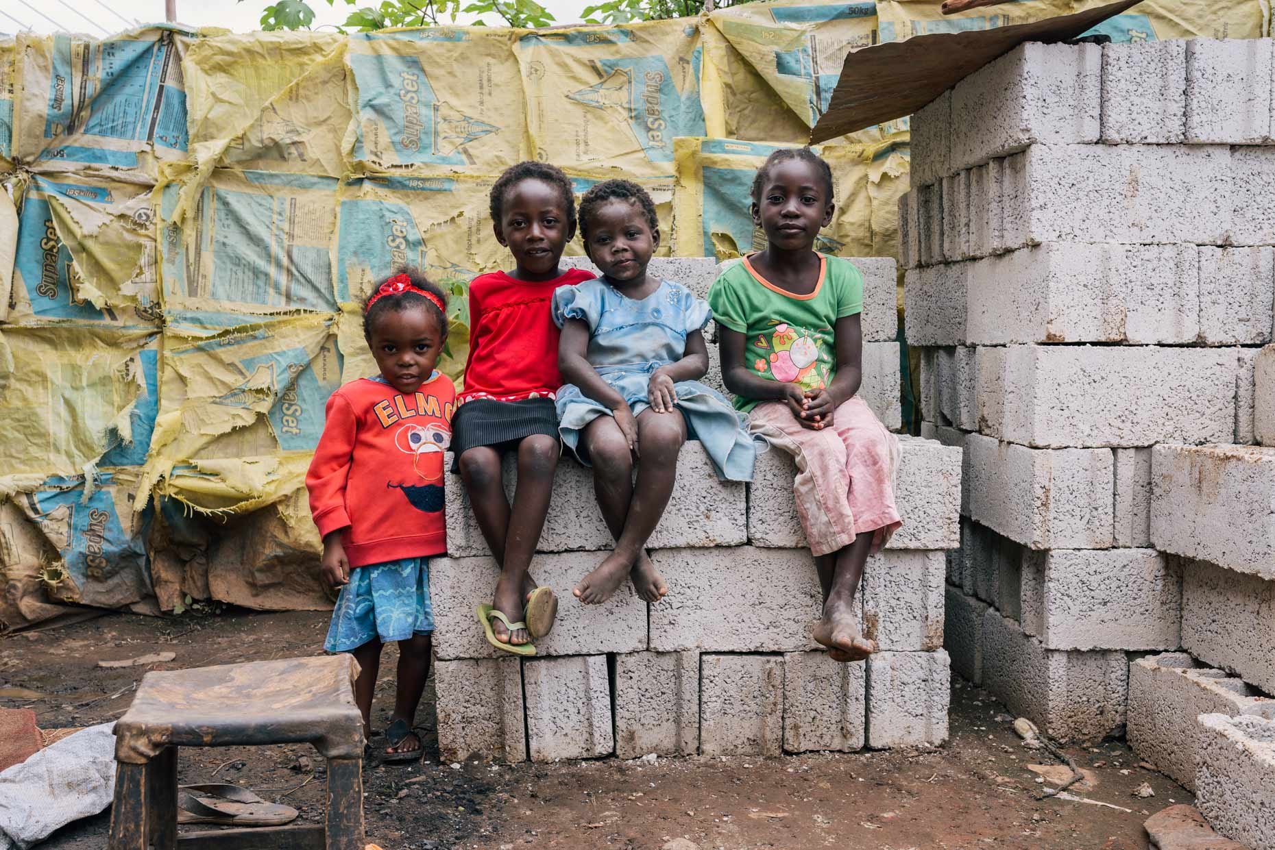 Environmental-portrait-of-four-girls-sitting-on-bricks-in-Africa-YES