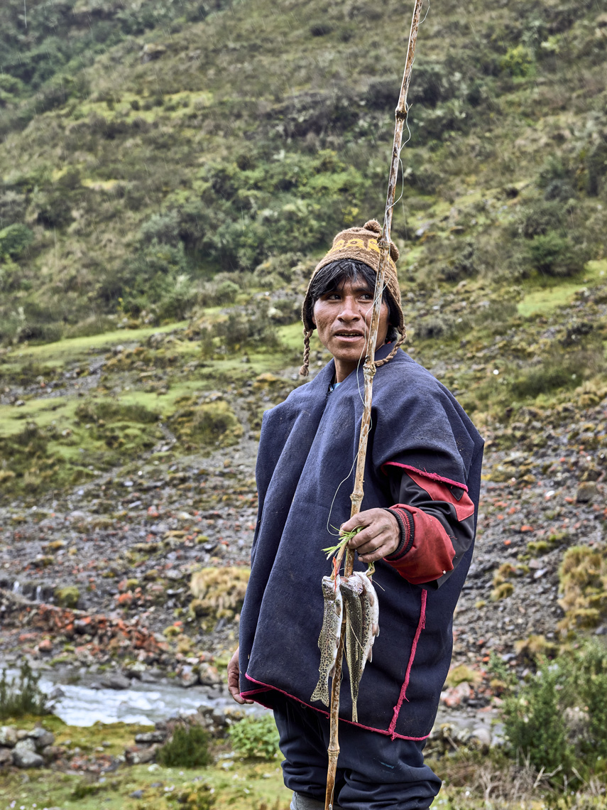 Local-Peruvian-villager-with-fresh-caught-trout-on-a-fishing-stick