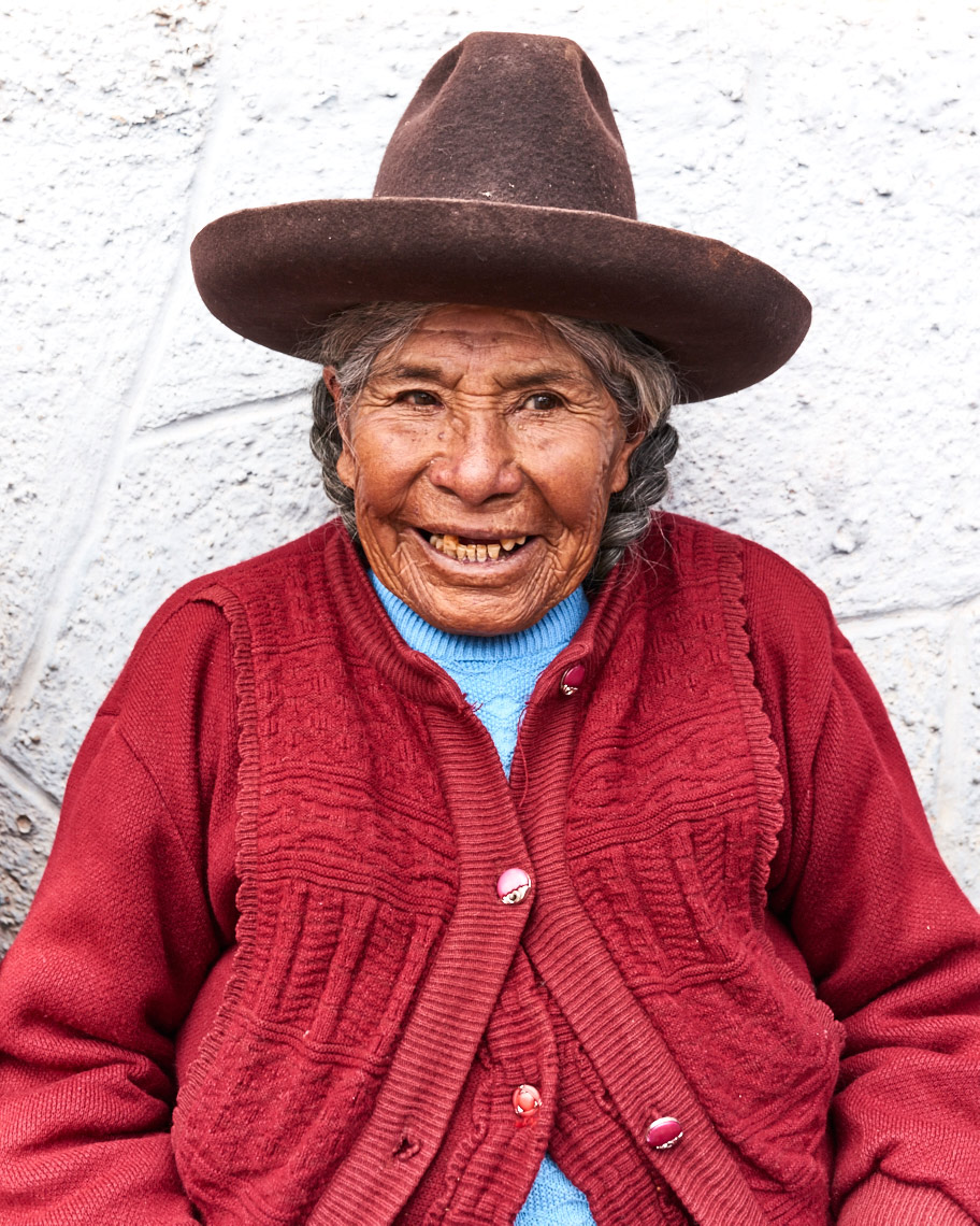 Local-Peruvian-woman-smiling-in-tall-hat-and-colorful-clothing-