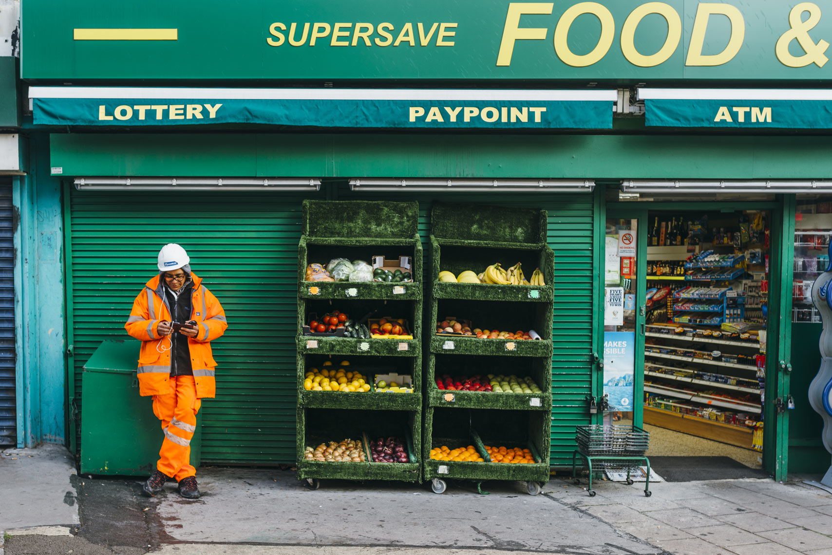 Man-in-orange-construction-uniform-stands-at-green-super-market