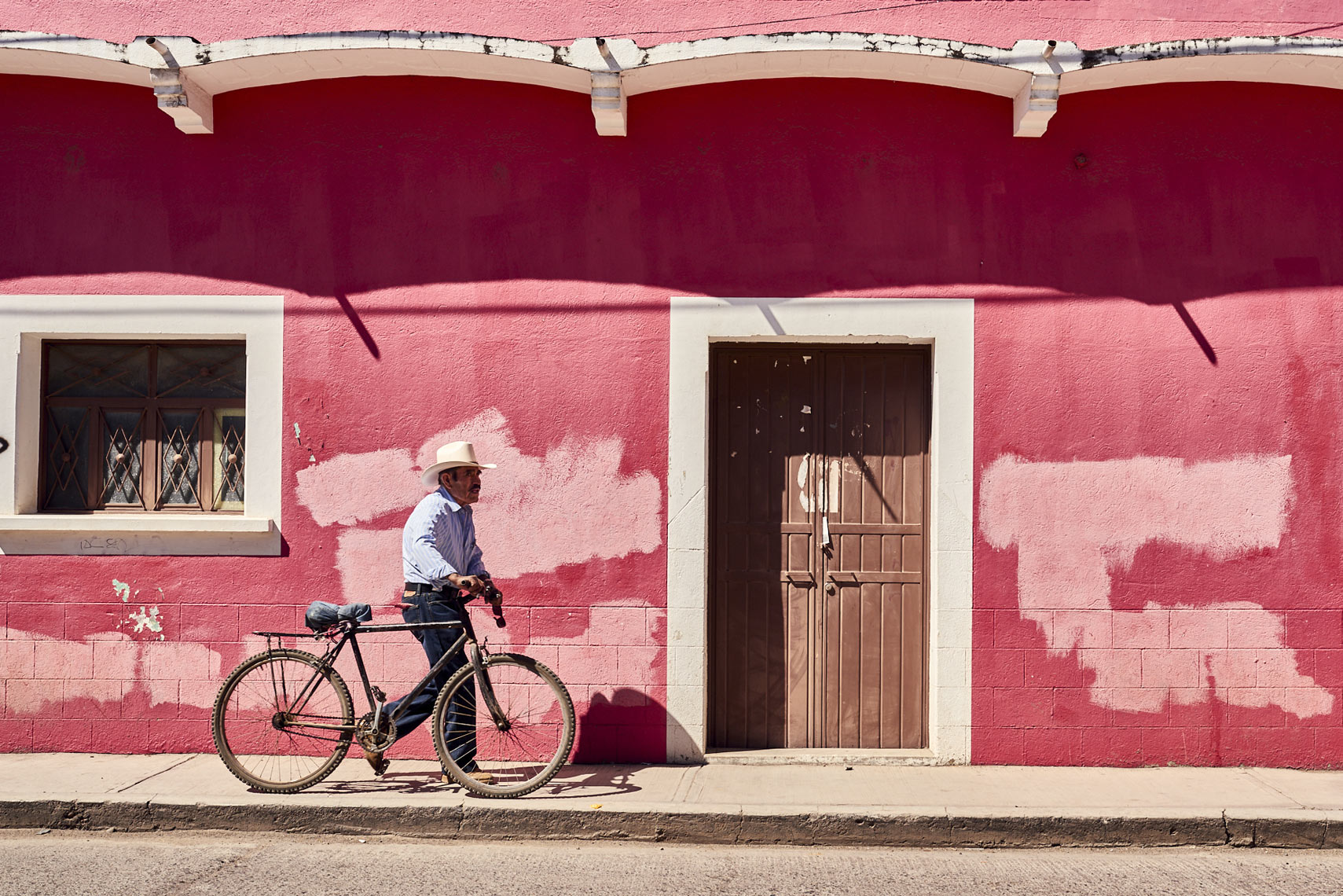 Mexican-man-walking-bike-along-pink-wall-in-Oaxaca