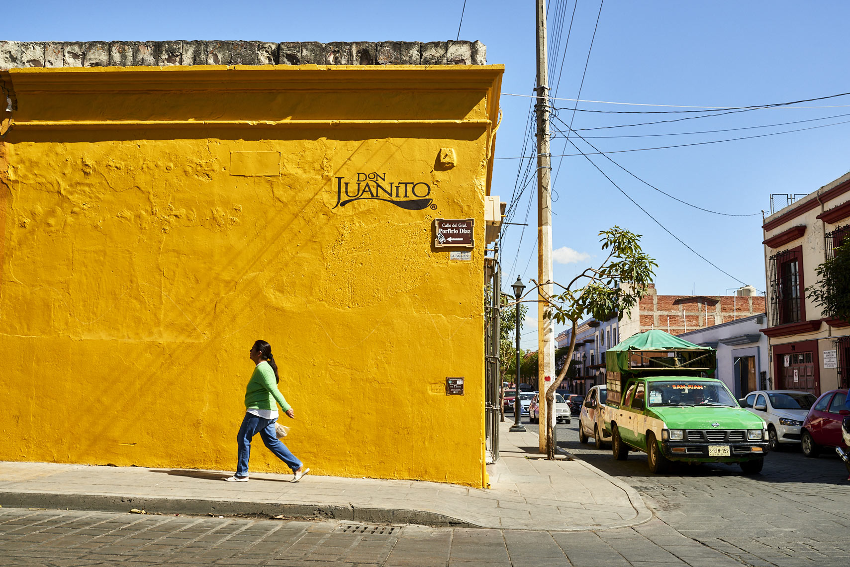Mexican-woman-walking-along-yellow-wall-in-Oaxaca