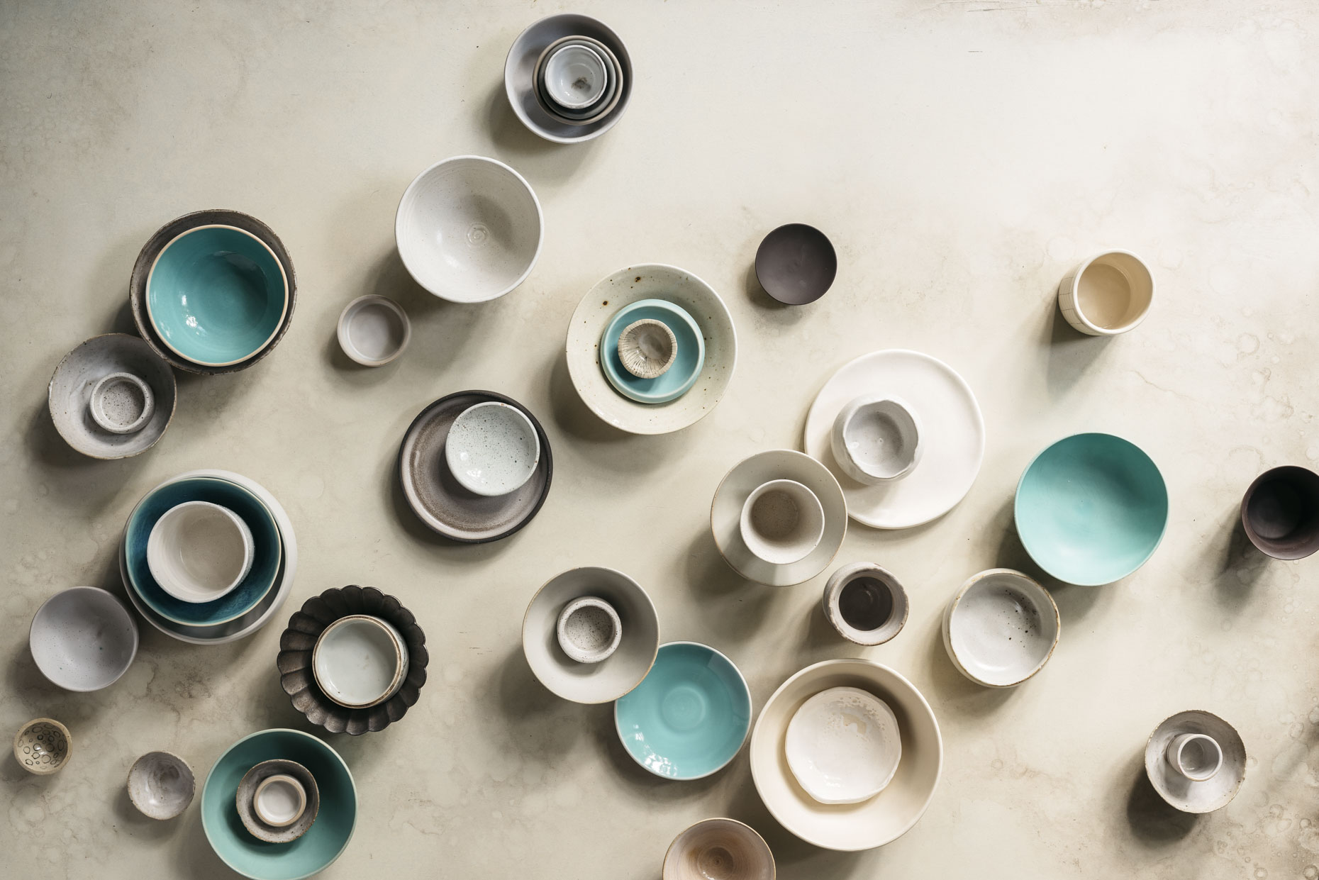 Modern handmade collection of ceramic cups, bowls plates collection on plaster table