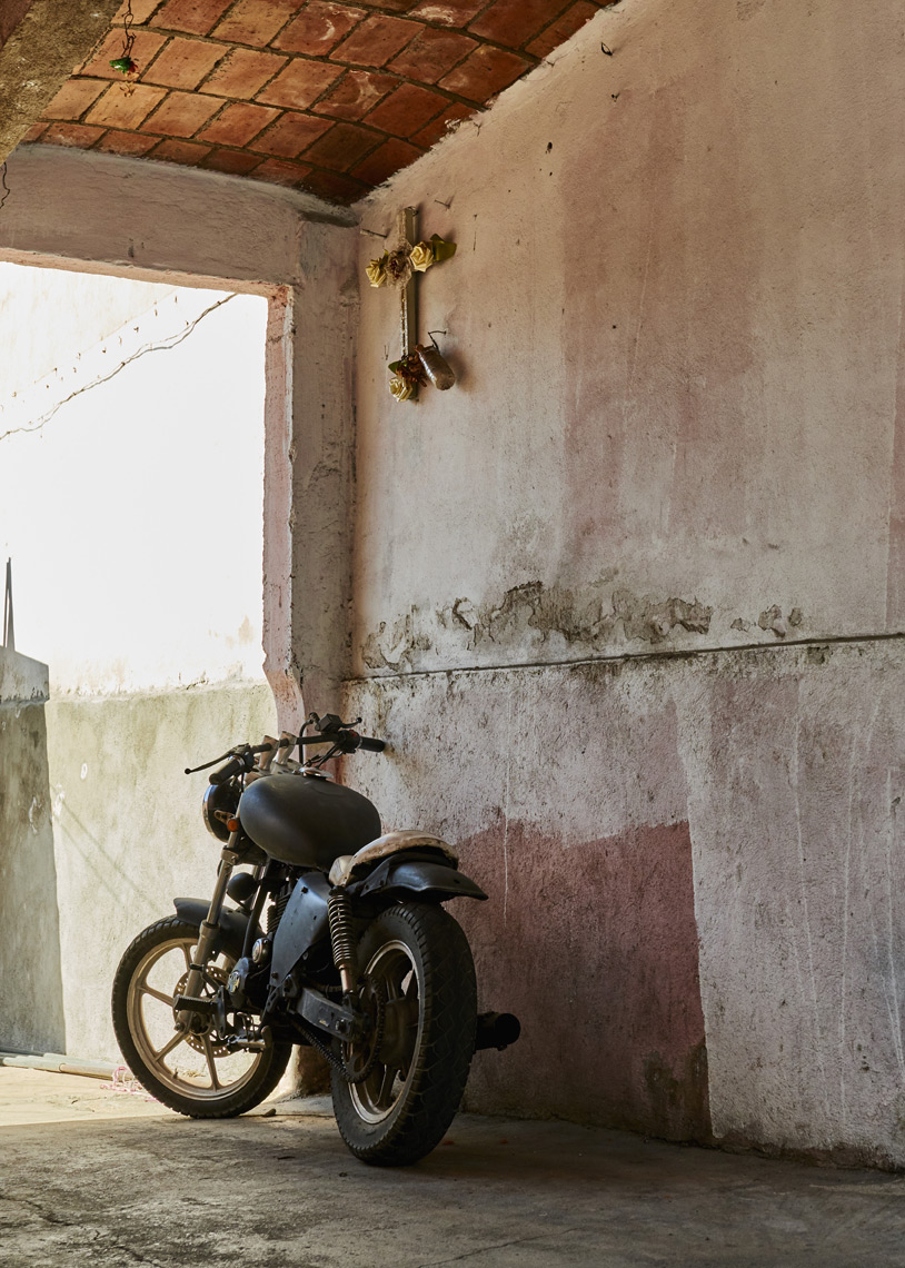 Motorcycle-parked-along-wall-under-cross