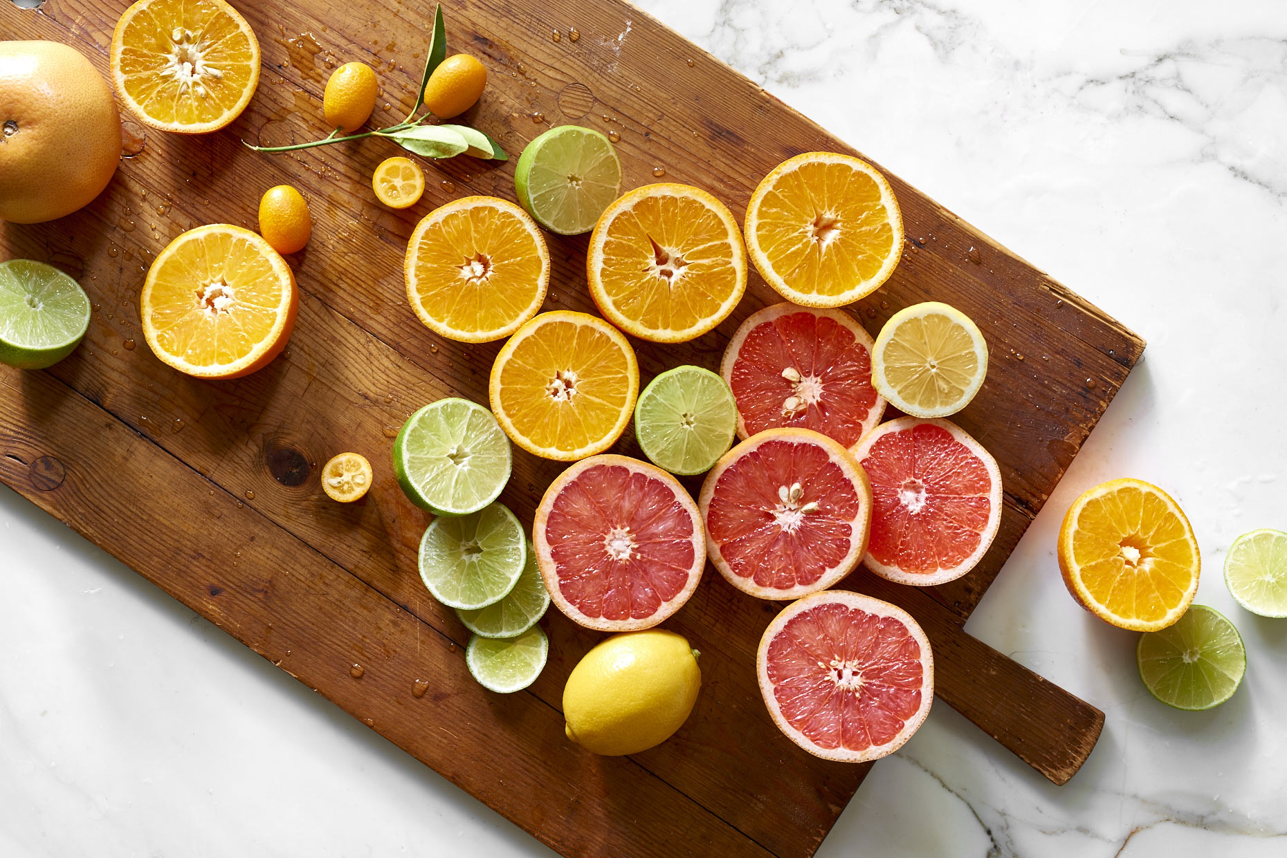 Oranges-lemons-and-limes-citrus-on-wood-cutting-board