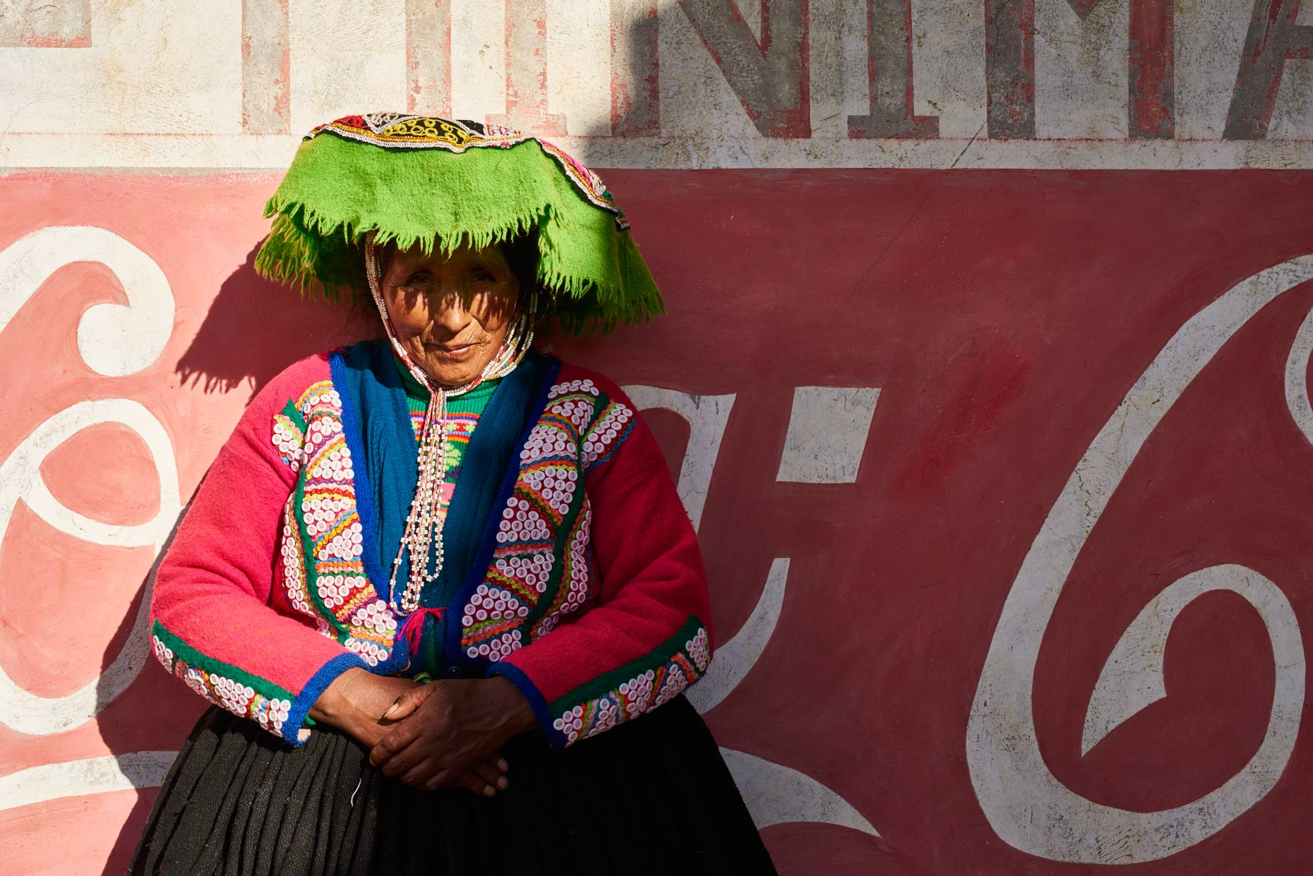 Peruvian-woman-in-colorful-attire-sits-against-Coca-Cola-wall
