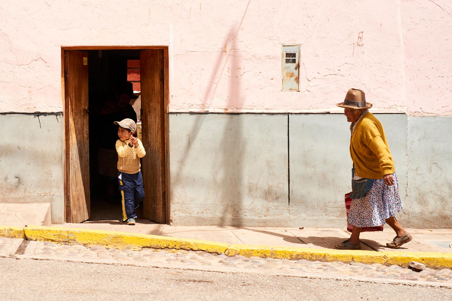 Peruvian-woman-in-tall-hat-walking-on-sidewalk-with-young-boy-in-doorway