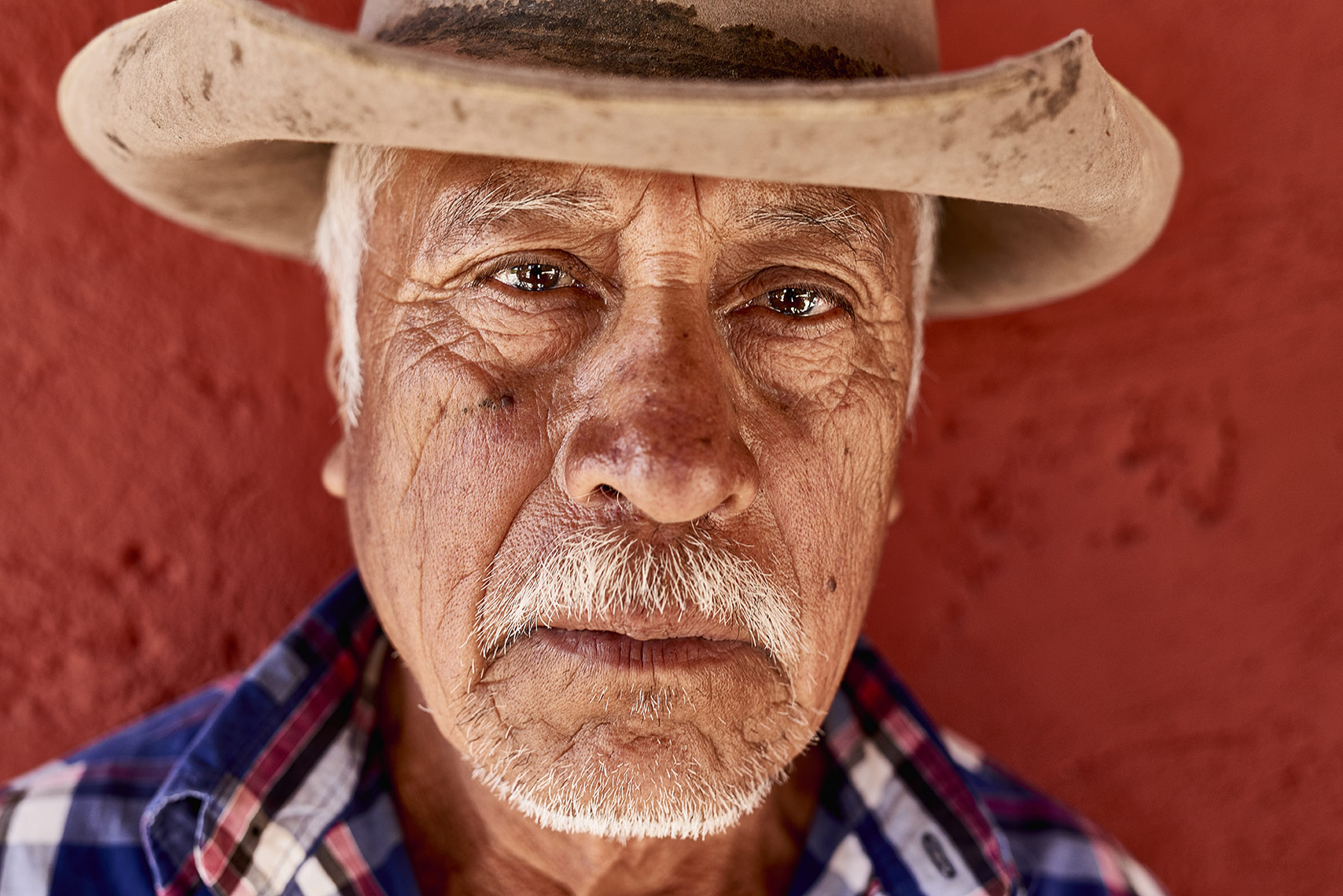 Portrait-of-adult-Mexican-farmer-on-red-wall