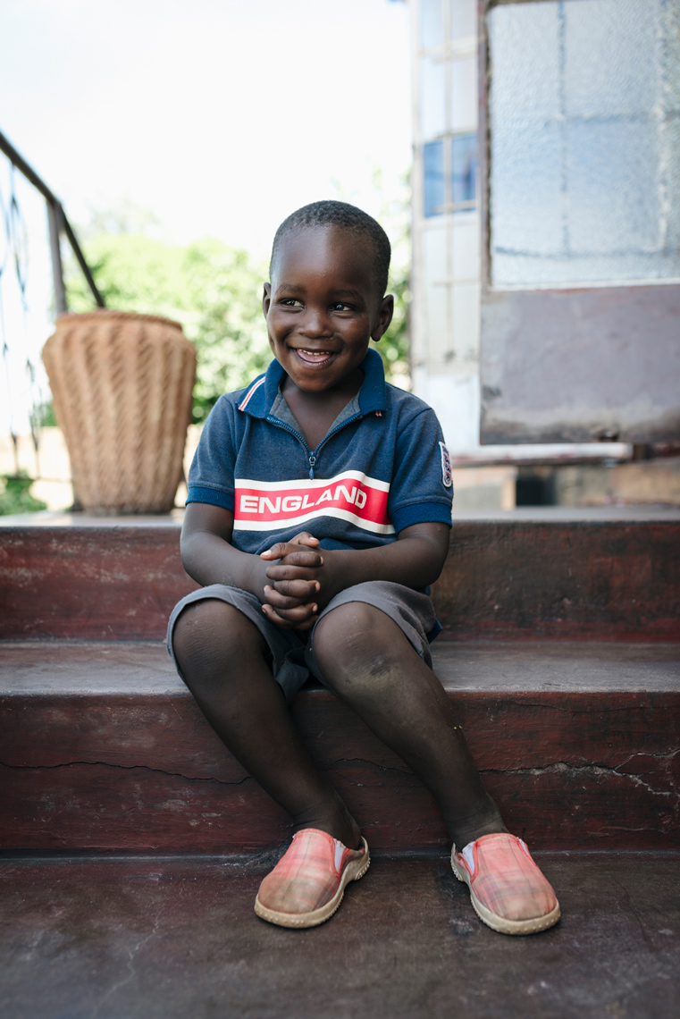 Portrait-of-happy-smiling-boy-sitting-on-steps-in-Africa-Yes