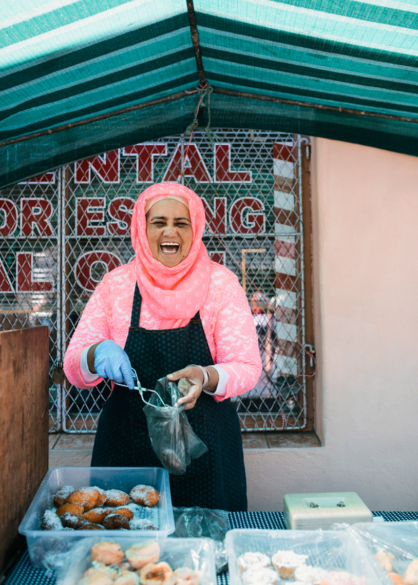 Portrait-of-laughing-Cape-Malay-woman-serving-at-market_YES