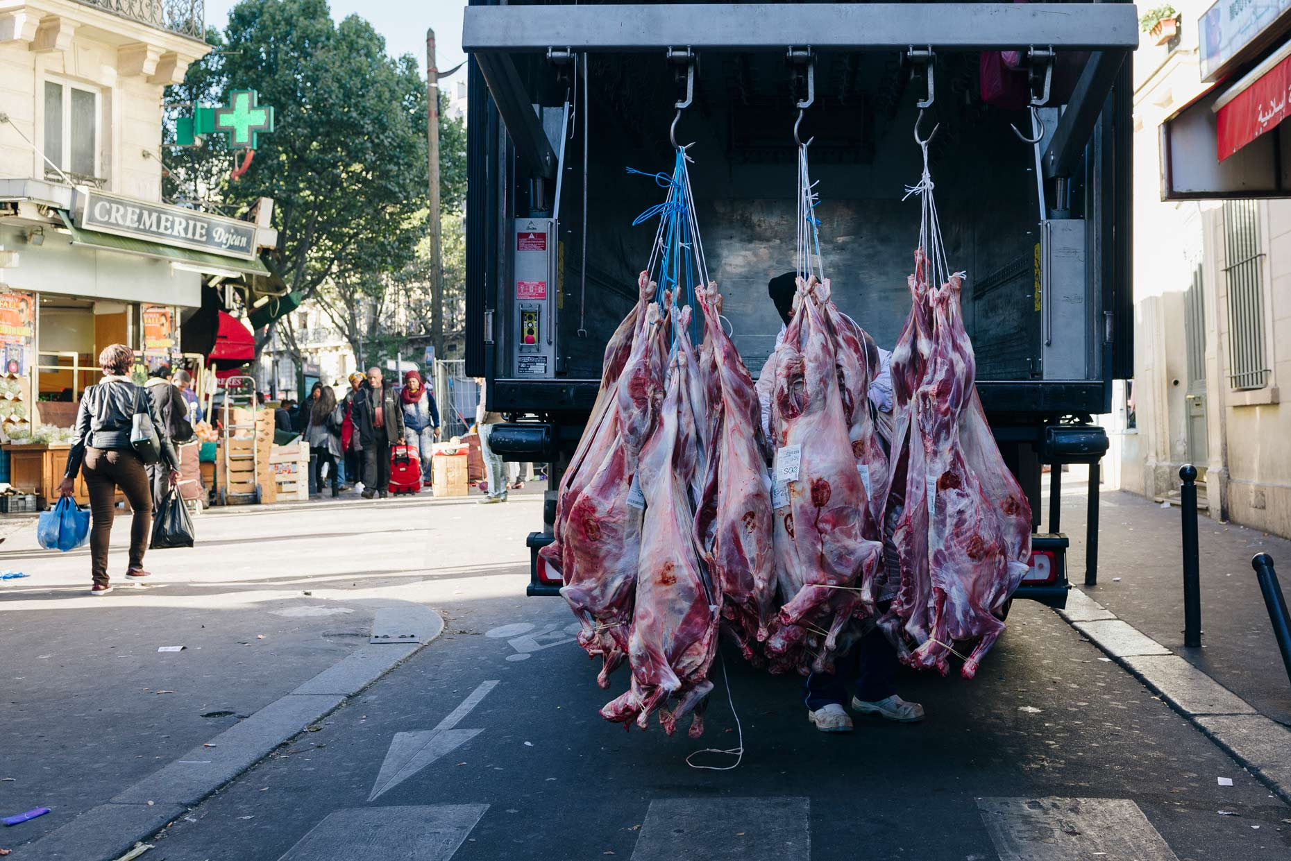 Sides-of-raw-meat-hanging-on-city-truck-at-butcher