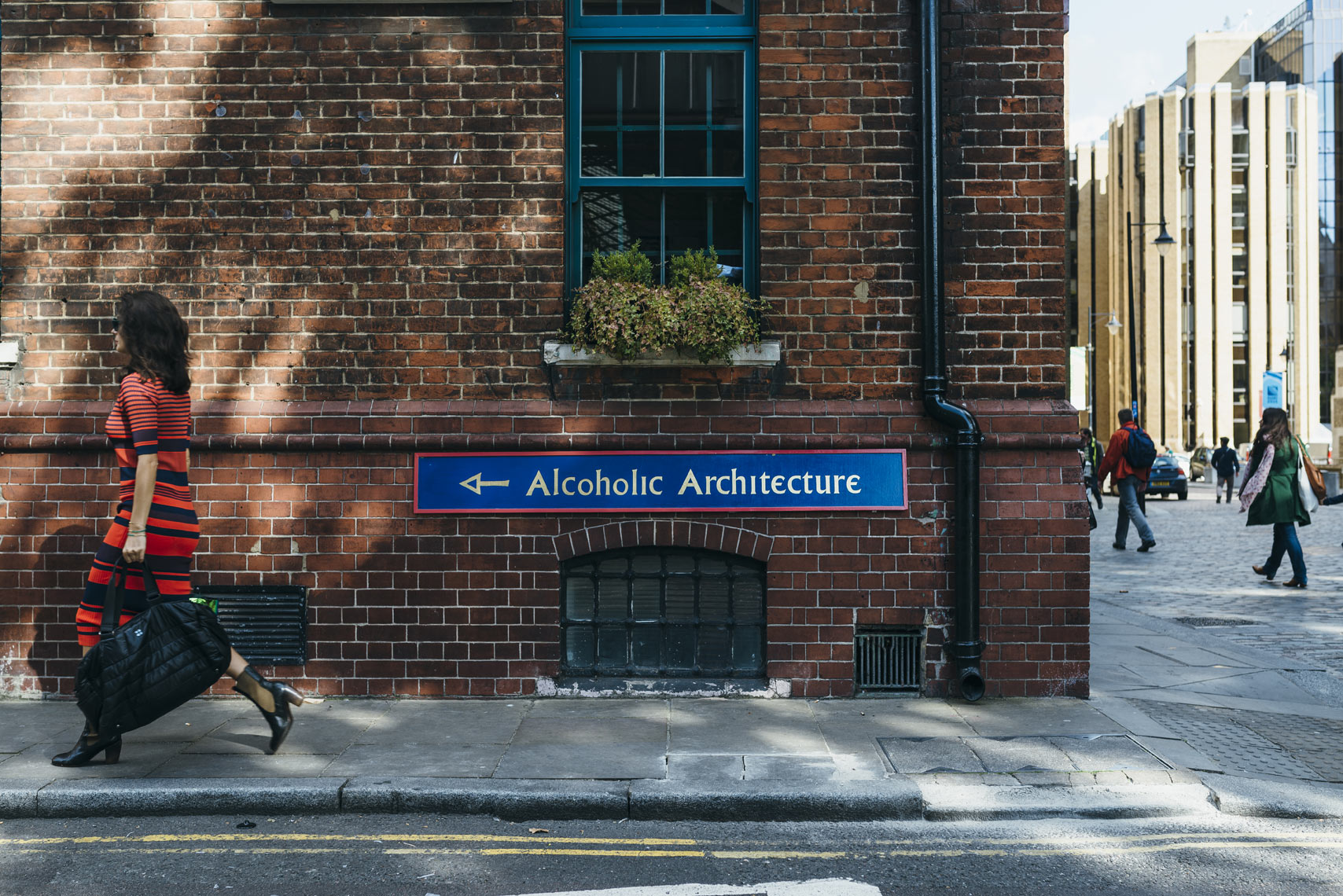 Stylish-woman-walks-by-Alcoholic-Architecture-sign-on-brick-building