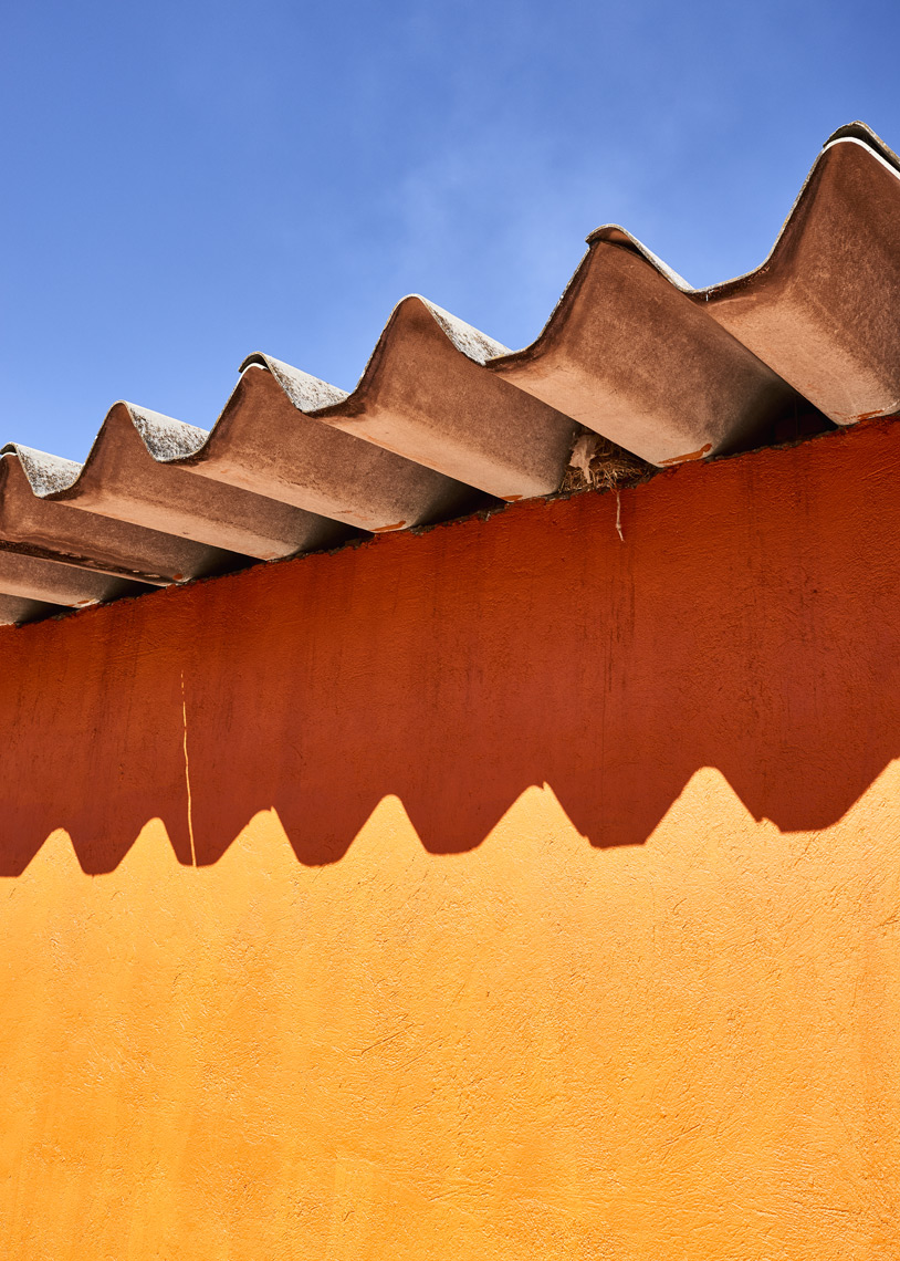 Tile-roof-shadow-on-orange-wall-blue-sky