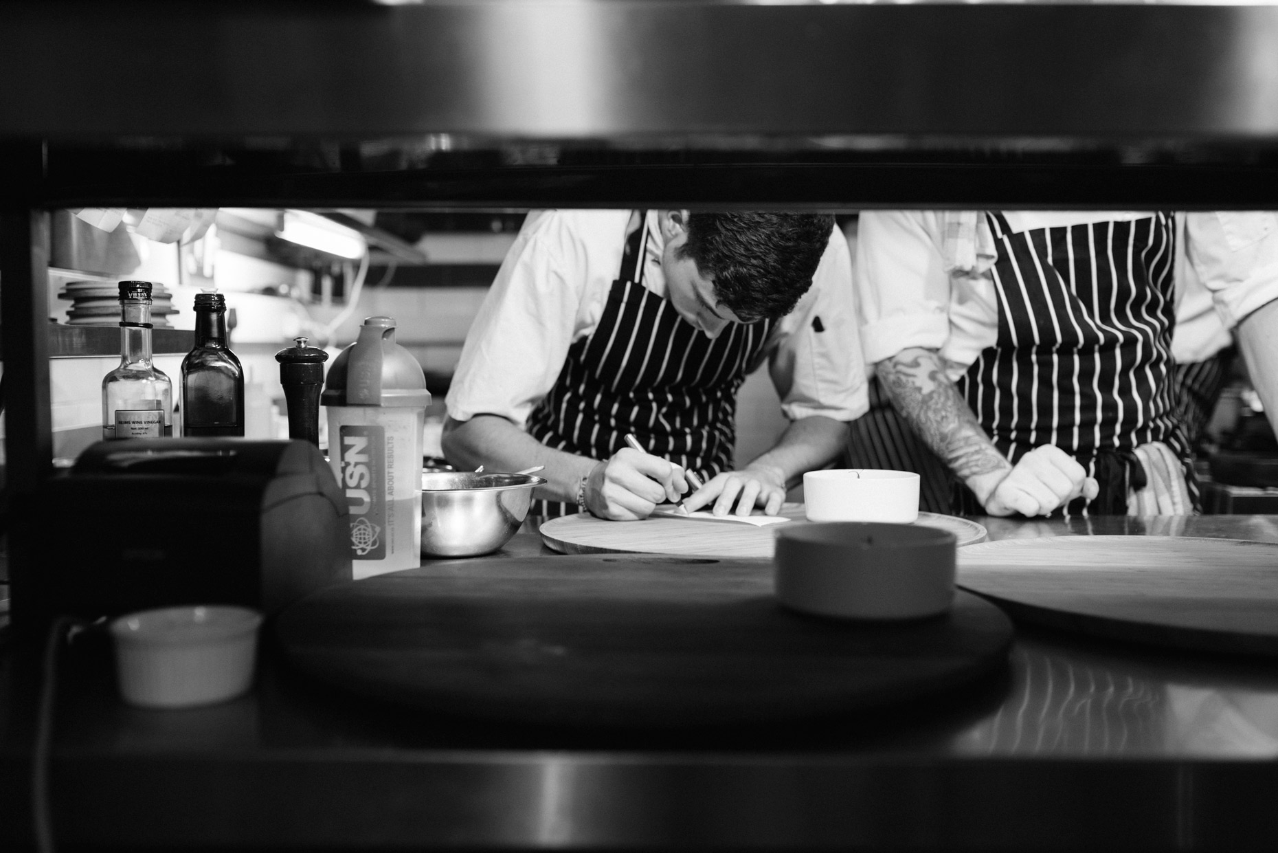 Two-chefs-in-Cape-town-restaurant-preparing-ticket_YES