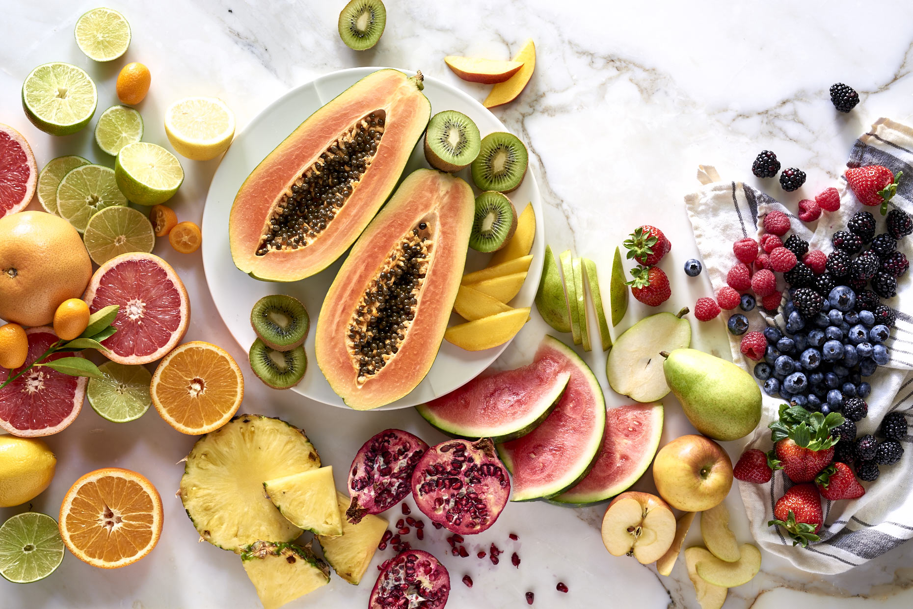 Various-healthy-fruit-cut-open-on-marble-table