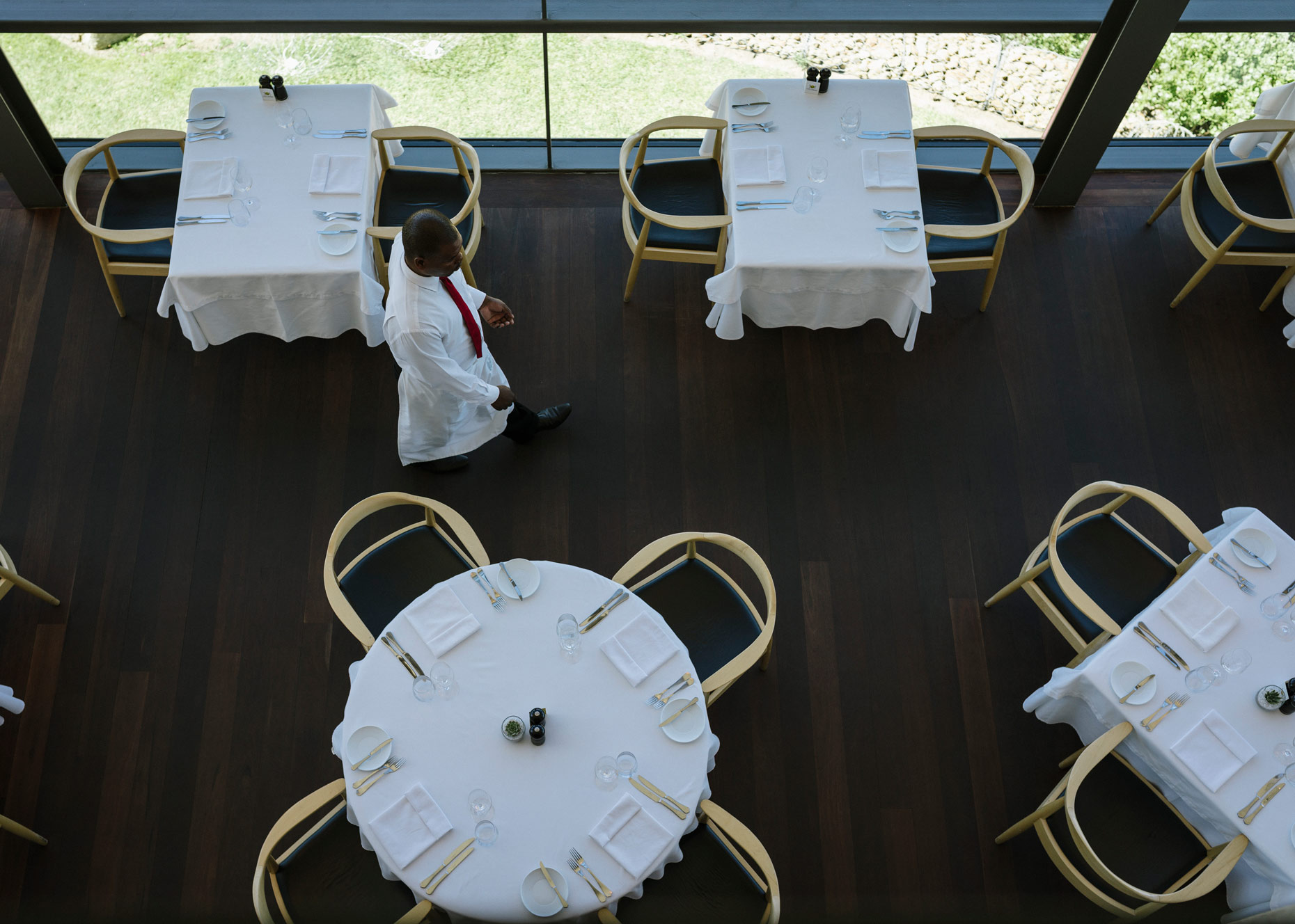 Waiter-serving-empty-white-tables-in-wine-restaurant-YES