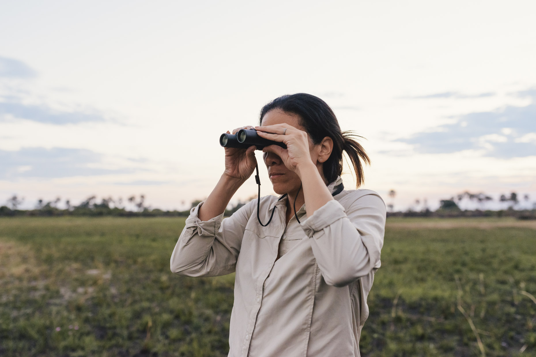 Woman animal watching in Leica binoculars on African safari