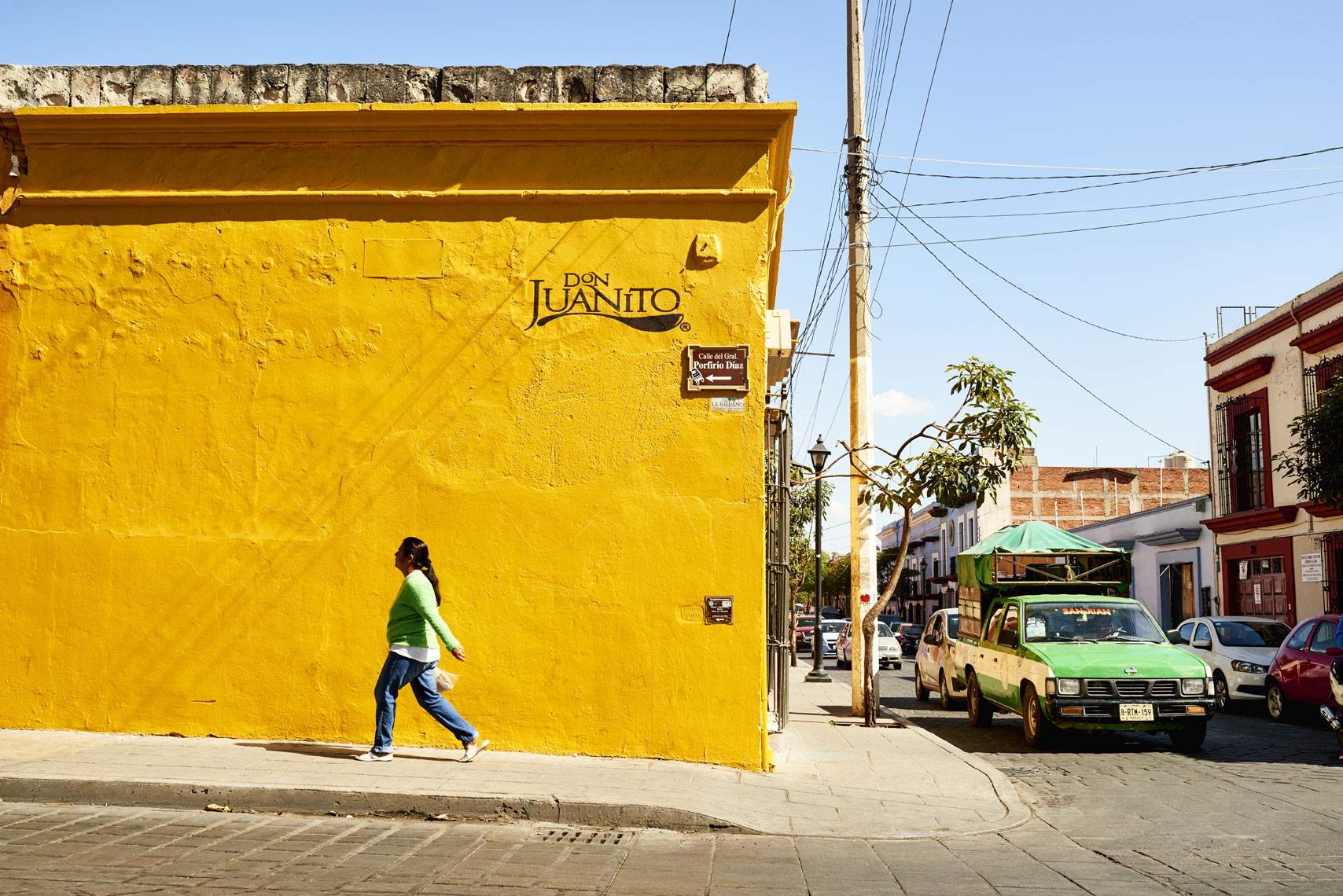 Woman-walking-along-yellow-wall-in-Oaxaca