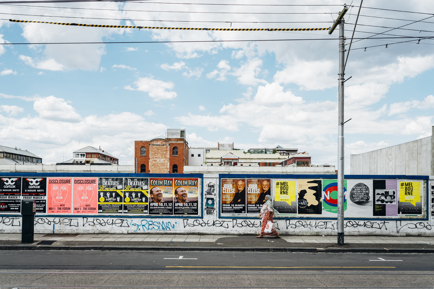 Woman-walking-on-sidewalk-against-wall-of-posters-in-Melbourne-Australia