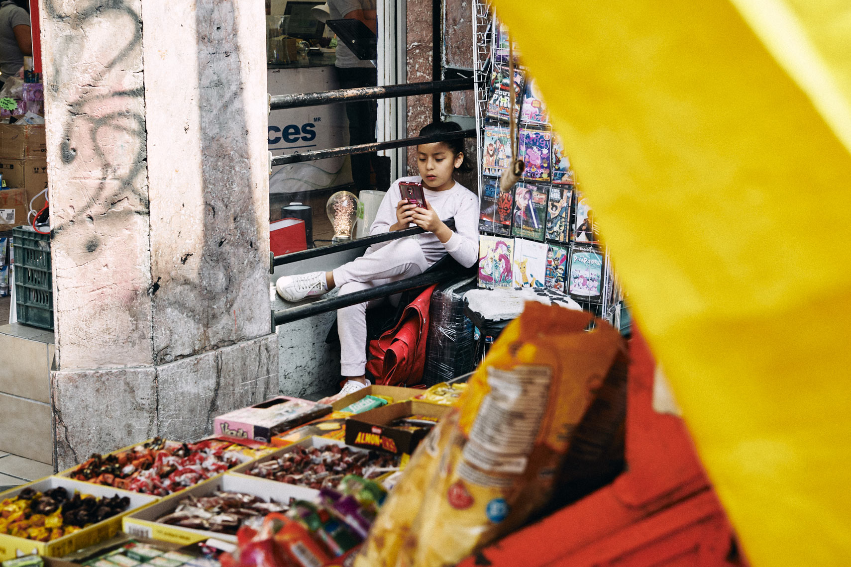 Young-Mexican-girl-taking-a-break-near-street-vendor